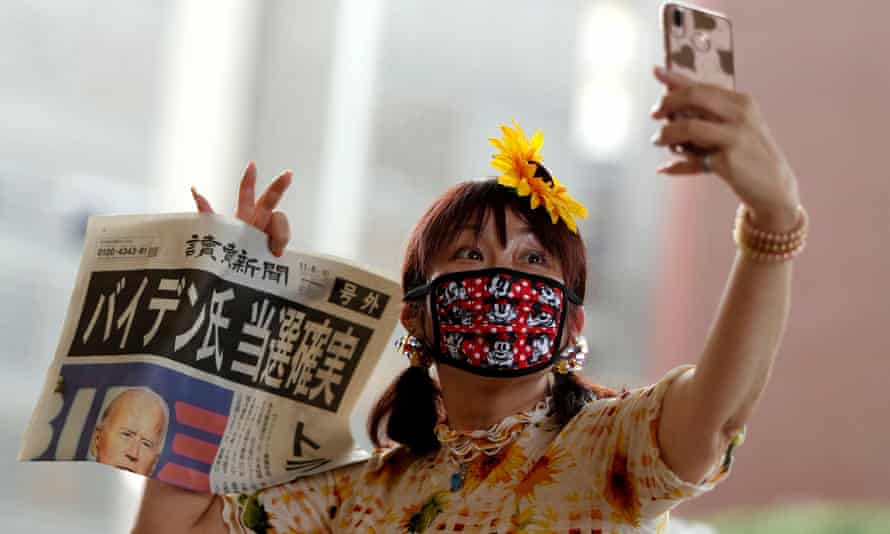 A woman in Tokyo takes a selfie with a newspaper reporting Biden's victory