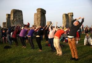 Amesbury, England People practice yoga at Stonehenge
