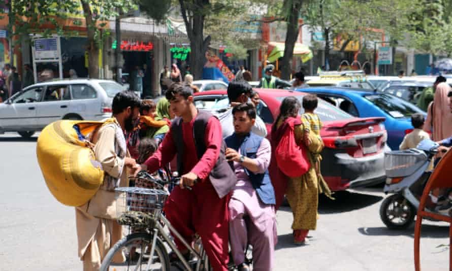 A boy on a bike and others on foot carry bags in a street in Kabul
