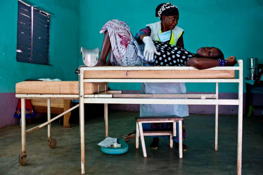 A woman is examined by a midwife at a health clinic near Doko, Siguiri, Guinea.
