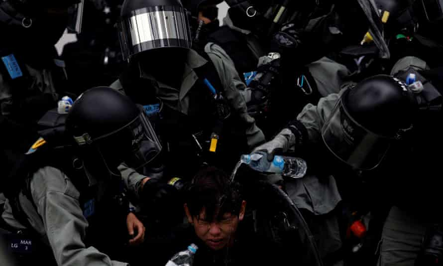 Police pour water on a protester who was pepper-sprayed while being detained in Sheung Shui, Hong Kong