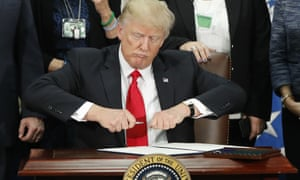 Donald Trump prepares to sign an executive order to build a border wall, on 25 January