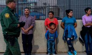 Migrants, mostly from Central America, wait to board a van which will take them to a processing center last month in El Paso, Texas.