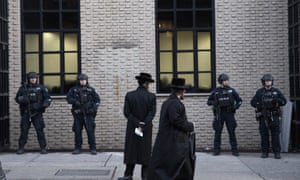 Orthodox Jewish men pass police guarding a Brooklyn synagogue prior to a funeral for a victim of the shooting inside a Jewish grocery, 11 December.