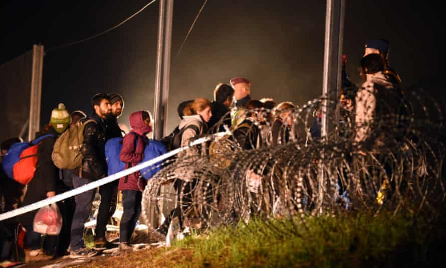 Migrants arriving from Croatia cross the border to Hungary before it was sealed with barbed wire early on Saturday.