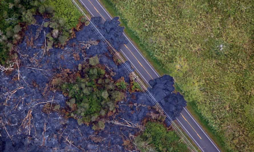Lava from the Kilauea volcano flows across a highway.