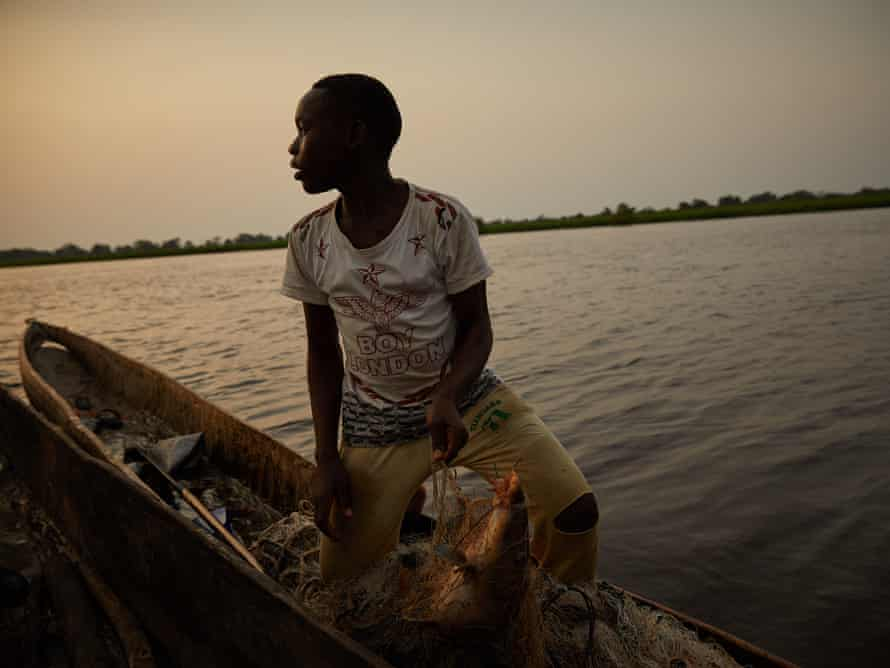 A boy sells his catch of the day mid-stream of the Congo River in Équateur province