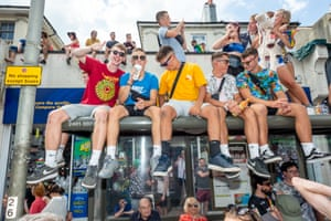A bus shelter becomes a sought-after vantage point as the parade passes