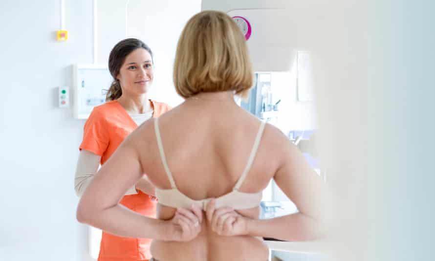 Nurse helps a patient prepare for a mammogram