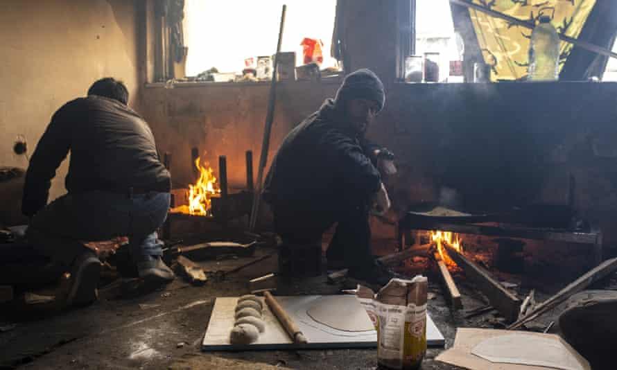 Afghan migrants cook inside an abandoned industrial plant in Bihać, Bosnia-Herzegovina