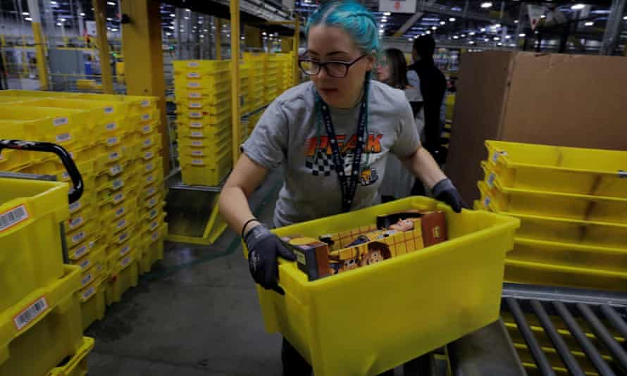 A worker moves a bin filled with products inside an Amazon centre in New Jersey.