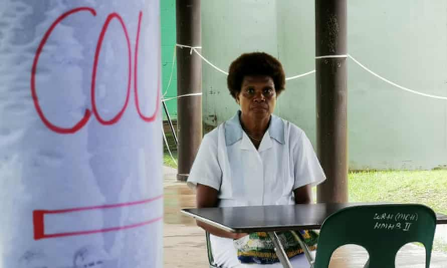 A nurse sits at a screening station for anyone presenting with a cough or flu like symptioms in PNG's East New Britain province.