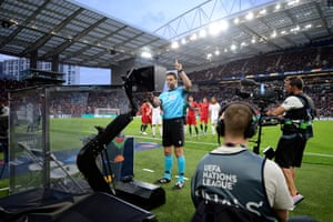 Referee Dr. Felix Brych checks the screen before awarding a penalty to Switzerland via VAR.