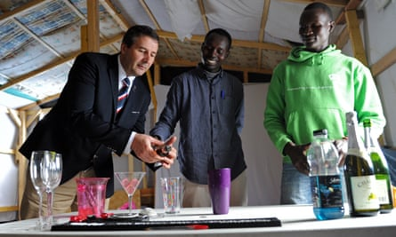 Gil Galasso, a specialist in tableware and cocktails, teaches two migrants from Sudan, Abdelrazic (right) and Jamal (centre) how to prepare cocktails.
