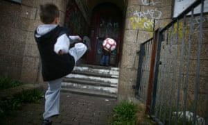 Boy kicking ball next to graffiti wall