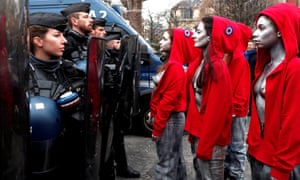 Women dressed as Marianne, a national symbol of the French republic, stand in front of officers.