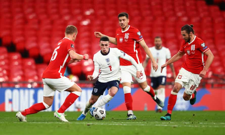England's Phil Foden runs with the ball under pressure from Jakub Moder and Grzegorz Krychowiak of Poland