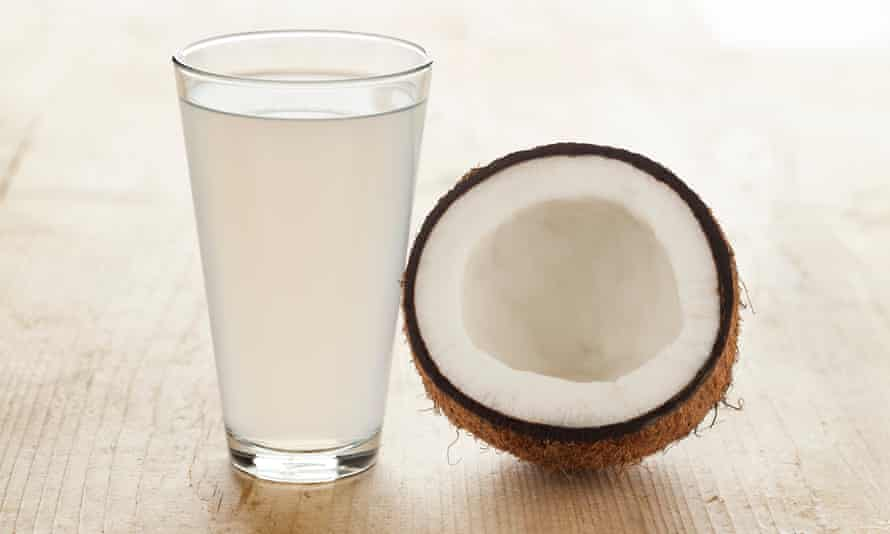 a halved coconut and coconut water in a glass