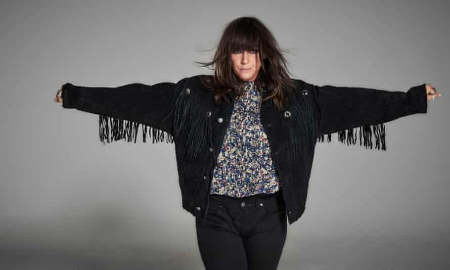 Cat Power with her arms outstretched in a blouse, denim jacket with tassels hanging from the arms and dark jeans