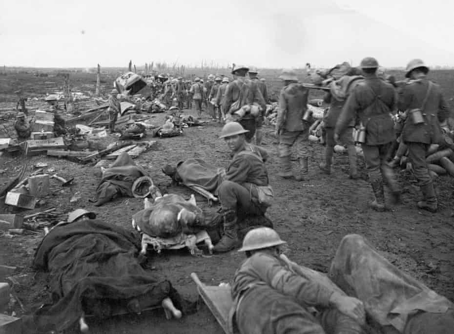 'Men wounded in the Ypres Battle waiting along the Menin Road to be taken to the clearing station. German prisoners are assisting with stretcher bearing.' 20 September 1917.