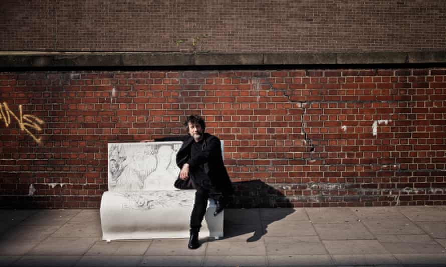 Neil Gaiman sits on a bench in London inspired by Neverwhere.