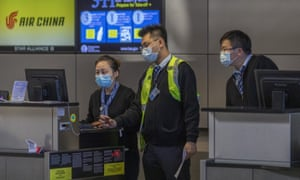 Air China employees wear medical masks for protection against the novel coronavirus outbreak at Los Angeles international airport.