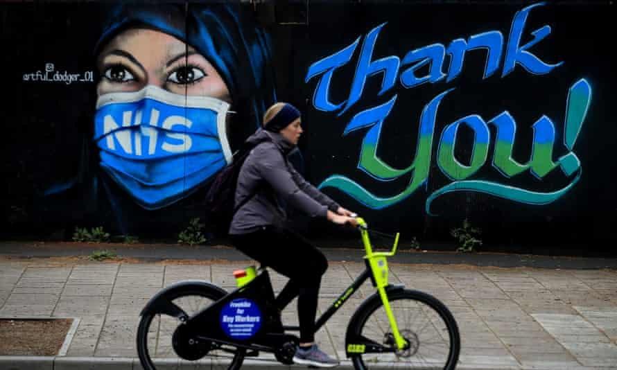 A woman cycles past a piece of street art, created by The Artful Dodger, thanking the NHS