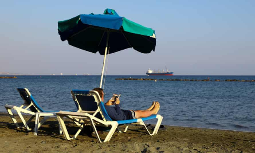 A man reads a book while sunbathing on a beach in Limassol, Cyprus.