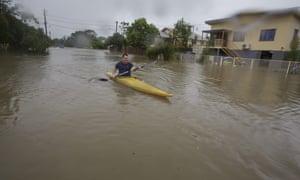 Graham Crighton kayaks in floodwaters in Hermit Park, Townsville