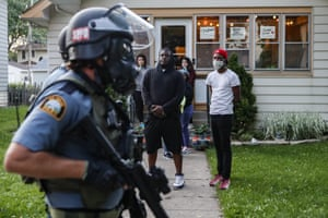 Protesters watch as police in riot gear walk down a residential street