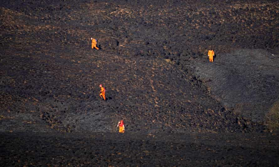 Firefighters make their way cross the charred moorland checking for pockets of heat.