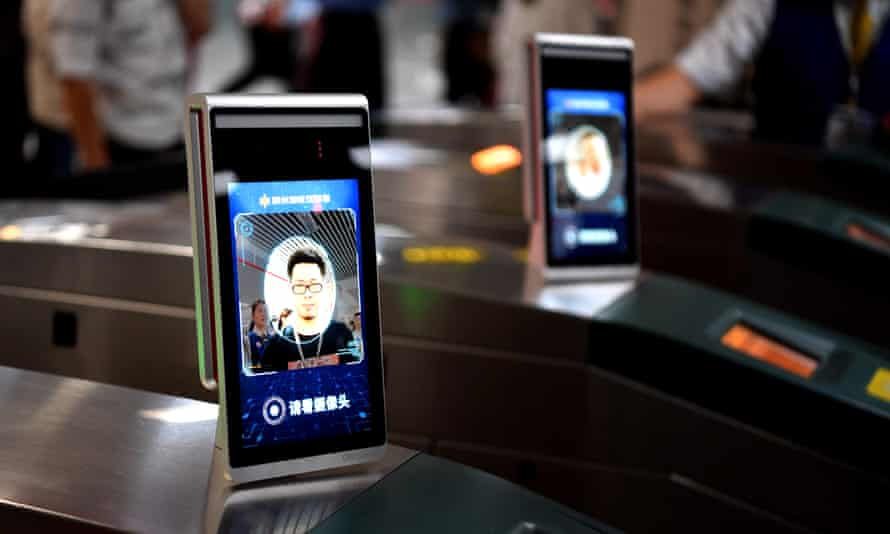 A man passes the ticket gate through facial recognition payment system at Zijingshan