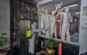 A worker disinfects statues at the National Centre for Social and Criminological Research in west Cairo