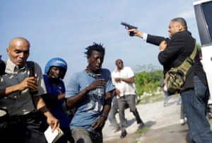 People flee as senator Jean Marie Ralph Fethiere fires a gun in the air amid chaotic scenes in Port-au-Prince, Haiti.