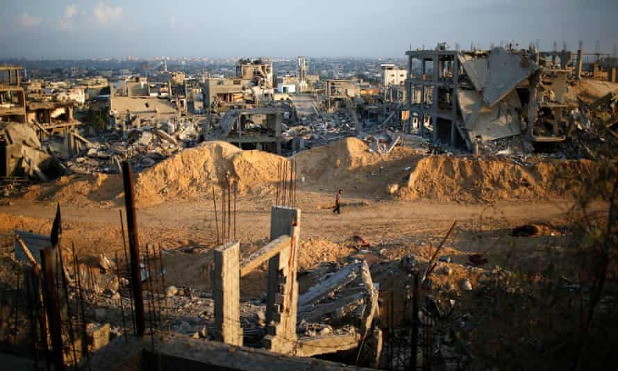 A Palestinian man walks past the ruins of houses in Gaza City
