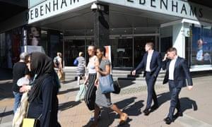 People walk by a London branch of Debenhams