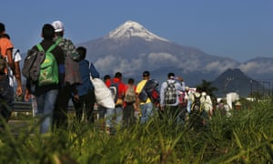 Central American migrants begin their morning trek as part of a thousands-strong caravan hoping to reach the US border, as they face the Pico de Orizaba volcano upon departure from Córdoba, Mexico, on Monday.
