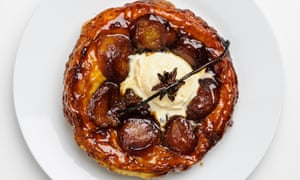 A round white plate with a caramelised round flaky pastry tart with apple halves and a scoop of vanilla ice-cream in the middle