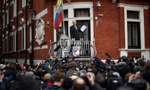 WikiLeak's founder, Julian Assange, holds up the UN panel's report as he addresses supporters and the media from the embassy balcony.