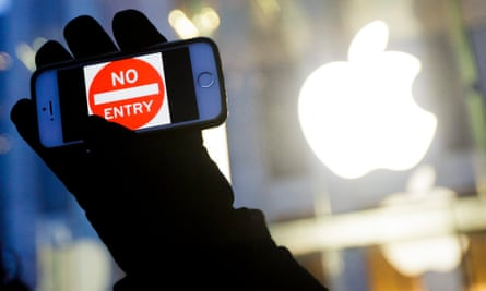 A man holds up an iPhone with a No Entry graphic