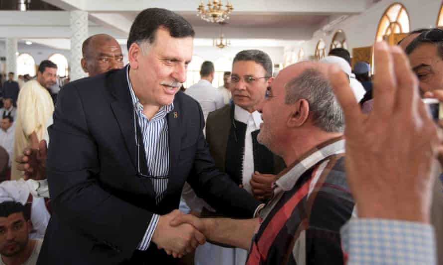 Fayez al-Sarraj (left) shakes hands with a man inside a mosque after Friday prayers in Tripoli earlier this month.