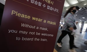 Visitors wearing face masks as a precaution against the coronavirus, walks past near a banner in Seoul, South Korea,
