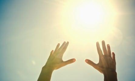 Woman's hands reaching toward sun