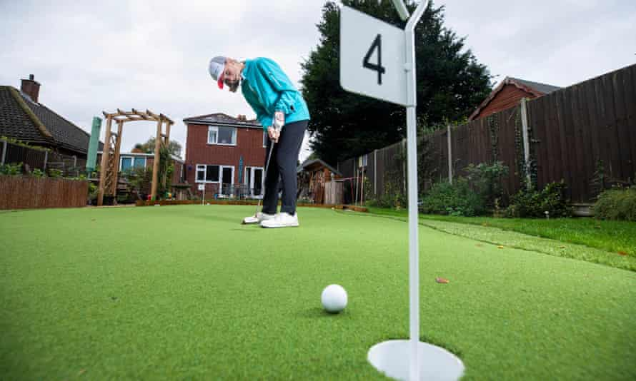 Lila Bisset, 11, plays a round of golf in her garden course in Rugby that her father, Paul, built.