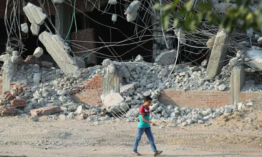 A boy passes demolished buildings in Saryaqos village, north of Cairo, Egypt,