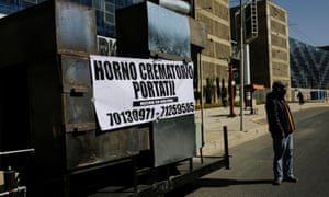 "A man stands near the prototype of a mobile crematorium with a banner reading ""Mobile crematorium, Made in Bolivia"", built by a local engineer to alleviate the backlog of bodies at local crematoriums, in La Paz, Bolivia 4 August 2020."