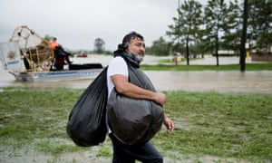 A man walks with belongings after being rescued from a flooded neighborhood in Houston.