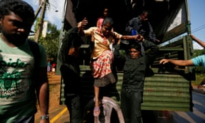 Sri Lankan army soldiers help a flood victim to get off from a truck during a rescue mission in Athwelthota village, in Kalutara.
