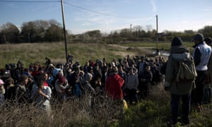 Refugees wait to board a bus near the dismantled camp in Calais.