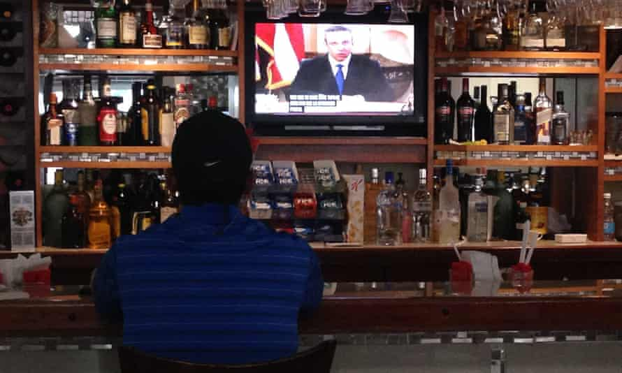 A man watches a TV broadcasting Puerto Rico's Governor Alejandro García Padilla delivering a televised message to the nation, in San Juan, on Monday.